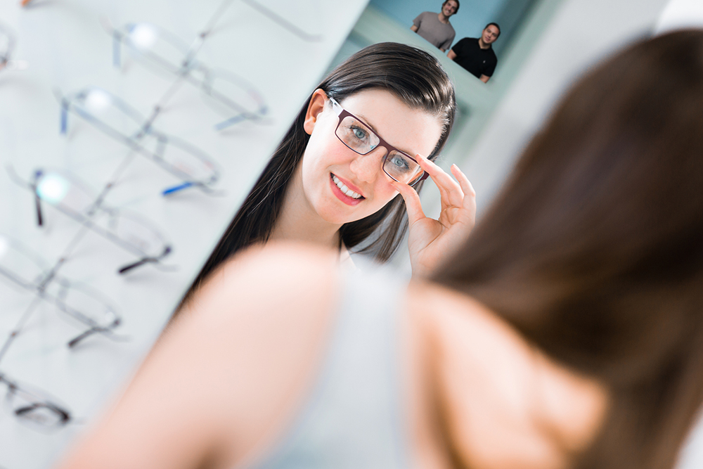 woman selecting some new eyeglasses from her optometrist